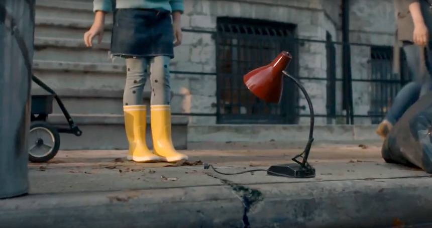 Girl in Rain boots stands next to red lamp