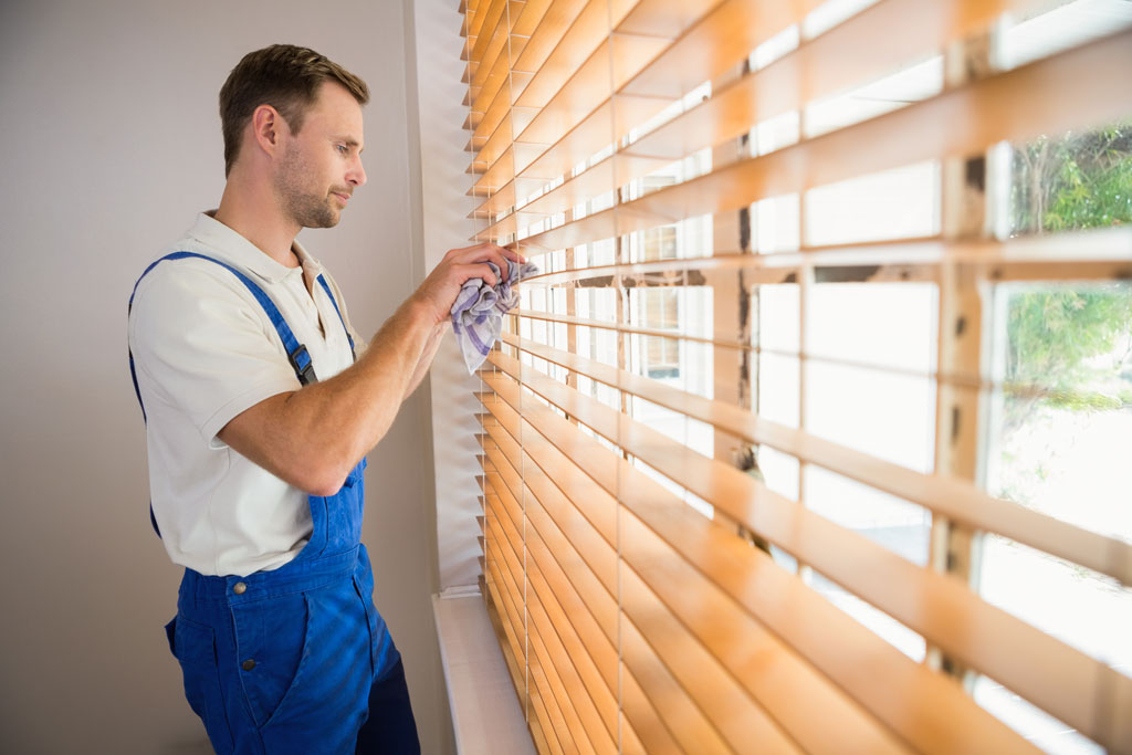 A man dusting off some blinds